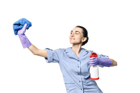 A beautiful young woman in the uniform of a maid holds a rag and spray for washing windows and looks at them in surprise. Isolated on a white background. Washes glass.