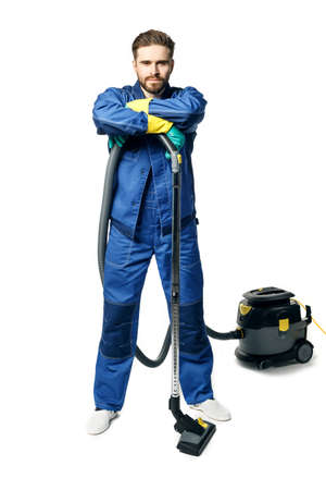 Young handsome man with a beard in a blue working uniform for cleaning rooms vacuuming isolated on white background. Stock fotó