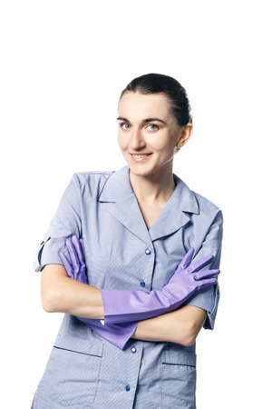 A beautiful young woman in the uniform of a maid smiling crossed her hands in rubber gloves on her chest. Isolated on a white background.