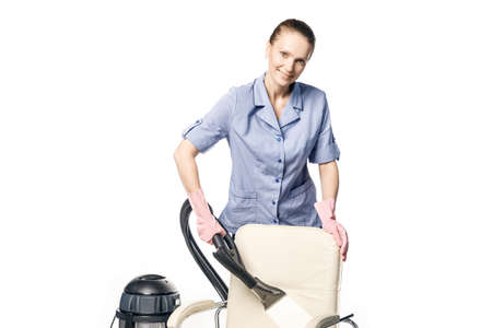 Young white woman in maid uniform is steam-cleaning an armchair isolated on a white background. Stock fotó