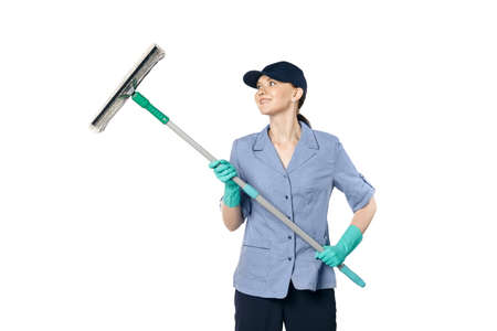 Brunette girl in a baseball cap and cleaning lady uniform washing a window with a special mop and smiles.