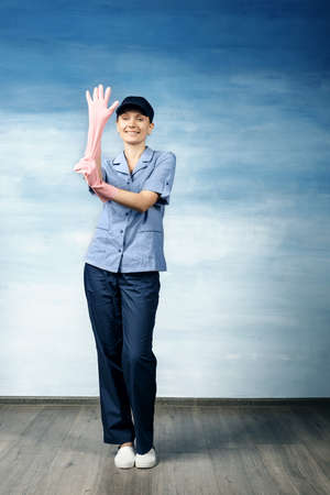 A beautiful young woman in the uniform of a maid and a baseball cap smiling and pulls on the glove on a blue background. Stock fotó