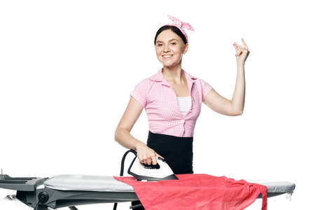 Snaps fingers. A beautiful girl dressed in pin-up style is ironing clothes looks at the camera and smiles isolated on a white background.