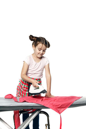 Little girl in an apron (mother's assistant), ironing things on an ironing board. She holds an iron isolated on a white background.