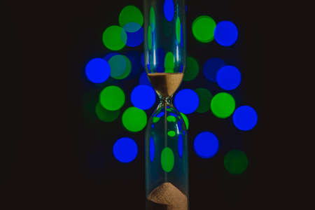 Hourglass in the right. Sand strews down on christmas background, bokeh blue, green, violet lights. Time flow. Time is over