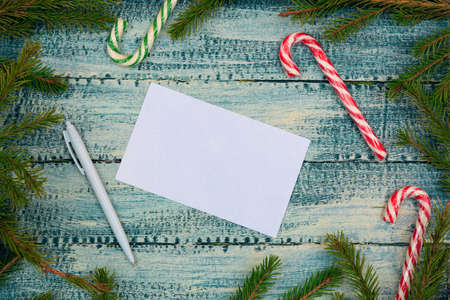 Christmas texture on a blue wooden background a piece of paper, a pen and candy canes surrounded by spruce branches. Stock fotó