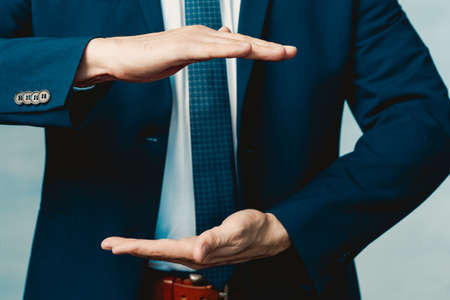 Hands of a man in a blue jacket folded in the shape of a sphere or as if pulling something.