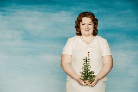 New Year freelancer corporate party. Funny plump red-haired girl in a white dress looks smiling broadly the pathetic Christmas tree in hands.