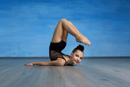 Acrobat standing in back bend pose on blue background. Yoga backbend gymnastics, girl gymnast in back bend bherundasana pose Stock fotó