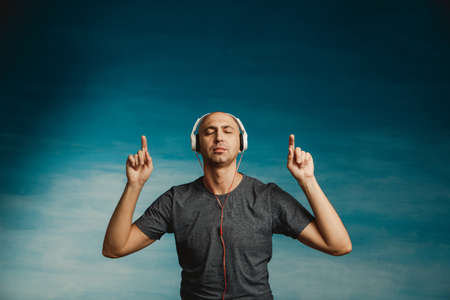 A bald man listens and enjoys music in large headphones with his eyes closed on a blue background. Dancing with closed eyes gesturing with his hands.