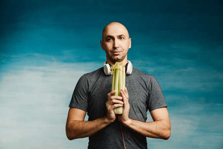 Funny bald man in headphones holds a celery on a blue background