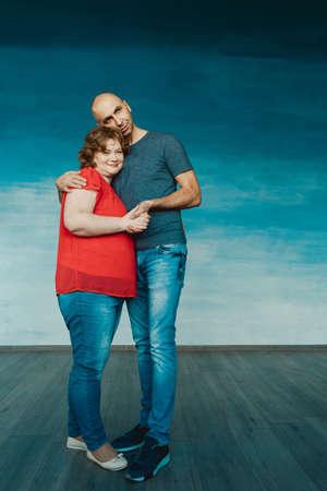 A tall bald man hugs an attractive chubby redhead woman against a blue background