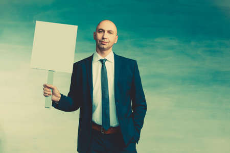 A bald man in a business blue suit spectacle and tie stands with holding a poster in his hand on a blue background Stock fotó
