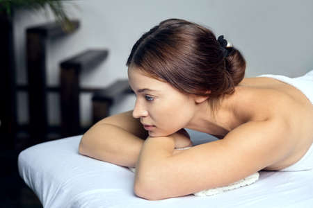 A beautiful young woman lies on her stomach during a stone massage.