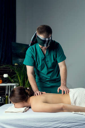 Masseur with blindfold doing blind massage of a young woman. Beautiful relaxed face of a young woman with brown hair and closed eyes