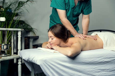 Massage therapist doing massotherapy of a young woman, elbow joint massage. Beautiful relaxed face of a young woman with brown hair and closed eyes.