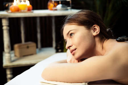 A beautiful young woman lies on her stomach during a stone massage