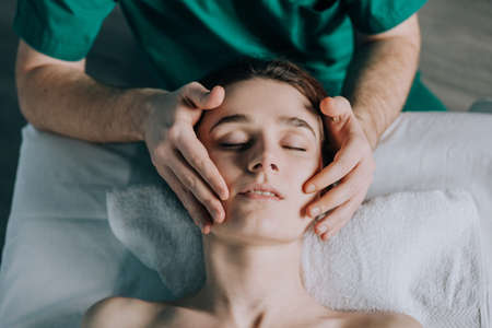 Face massage. Male hands make head massage to a beautiful young woman. Close-up of a woman getting spa treatment