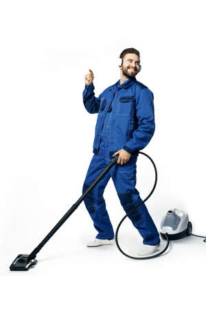 Young handsome man in working uniform for cleaning rooms listens to music with headphones smiling and vacuuming isolated on white background.
