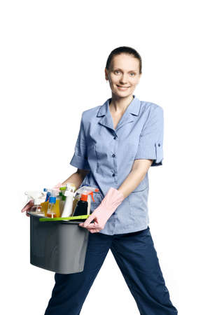 Attractive young woman in cleaning uniform and rubber gloves holding a bucket of cleaning products in her hands, isolated on white background