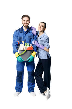 A young bearded smiling man in the uniform of a janitor holds a basket with moisturizing products, and maid-shaped women lean on his shoulder. Isolated on a white background