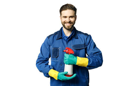 Young handsome man with a beard in a blue working uniform for cleaning rooms in rubber gloves and a janitor's uniform holds chemical spray bottle for cleaning. Isolated on a white background. Stock fotó