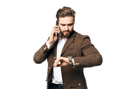 A portrait of a young handsome male businessman with a beard who is talking on the phone and looks at the clock. Isolated on a white background.