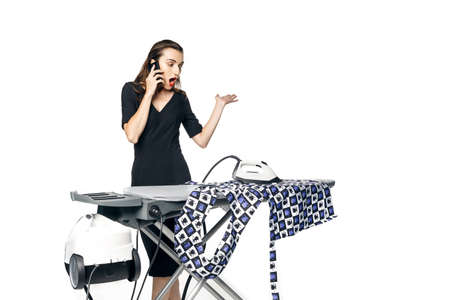 A young brunette business woman in a black dress is talking on the phone and stroking underwear, but burned through the fabric. Isolated on a white background.