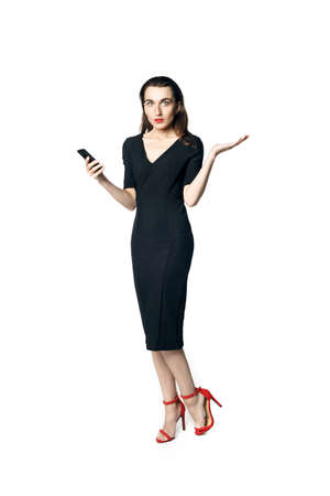 Business woman (fatal woman) in a black dress with red lipstick talking on the phone, isolated on a white background.
