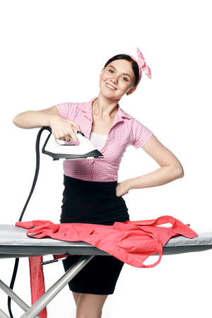 A beautiful girl dressed in pin-up style is ironing clothes isolated on a white background. Stock fotó
