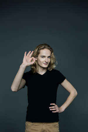 Young attractive guy with long blonde hair shows his ok sign on a gray background. Stock fotó