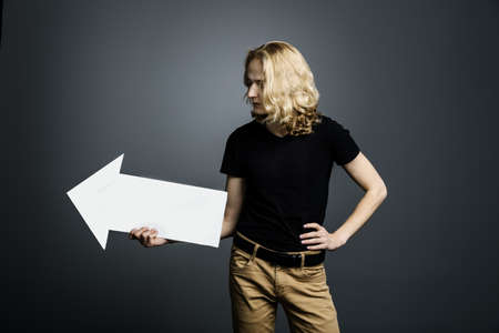 A handsome young guy with long blonde hair holds a white arrow pointing to the right on a gray background