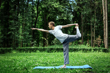 Young attractive man in a gray T-shirt and sweatpants doing yoga pose in the park. Keeps balance on one leg