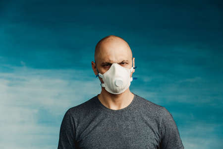 A bald man in a respirator on a blue background menacingly looks sneakily