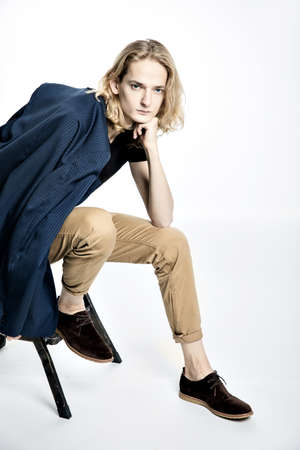 Handsome sad young guy with long blond hair sitting with his head elbows on a fist isolated on a white background.