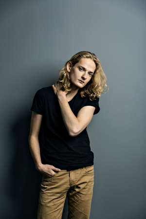 Young attractive guy with long blonde hair is sad leaning against a gray wall, looks to the camera.