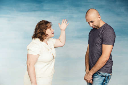 A plump red-haired attractive woman and a tall bald man on a blue background, the wife scolds her husband and screams at him with a wave of his hand, he stands with his eyes downcast.