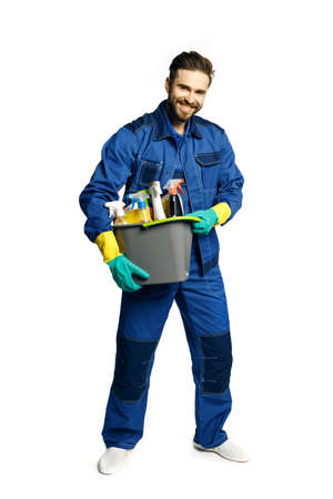 Attractive young man in cleaning uniform holding a bucket of cleaning products in his hands, isolated on white background.