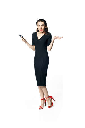 Business woman (fatal woman) in a black dress with red lipstick talking on the phone, isolated on a white background. throws up his hands in surprise.