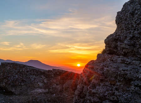 The rays of the setting sun make their way through a piece of rock Standard-Bild
