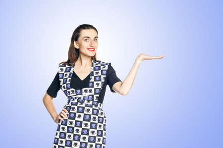 Beautiful woman in a black dress and a home apron for cleaning on blue background, one hand on the waist.