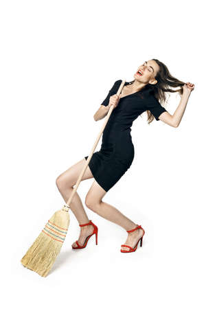Beautiful brunette woman in black dress and red shoes sings and dances with a broom, like a housewife, isolated on a white background. Standard-Bild
