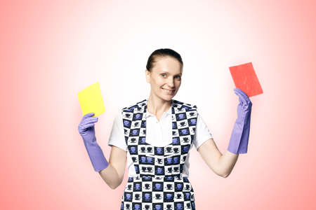A beautiful young woman in the uniform of a maid holds a rag for washing windows. Isolated on a white background.