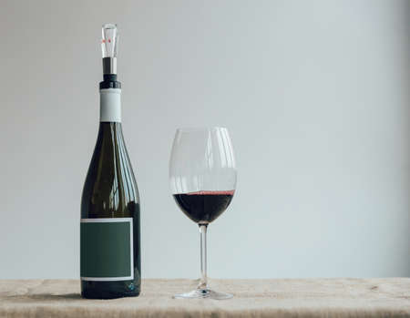 A bottle and glass of red wine on white background.