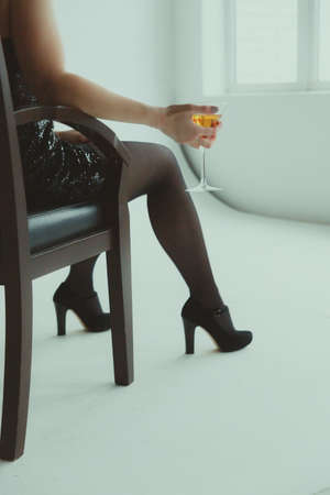 Female hand holding a martini glass while sitting in a chair.