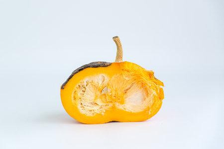 Spoiled orange pumpkin in a cut on a white background.