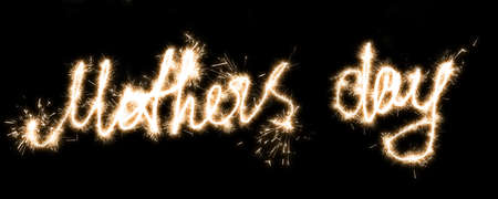 The inscription Mothers day on a black background with sparklers using a simulated long exposure. Standard-Bild