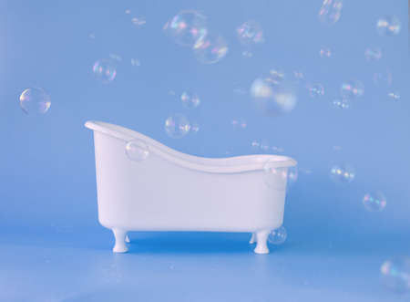 Empty white bathtub toy on a blue background and soap bubbles foam