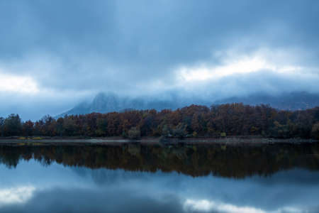 Mountains in the clouds against the blue twilight skyreflected in the lake Standard-Bild