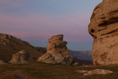 Evening mountain landscape, sunset purple sky between large boulders